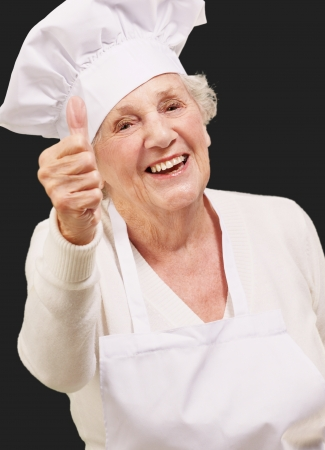 portrait of cook senior woman doing approval gesture over black background photo