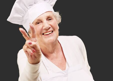 portrait of cook senior woman doing approval gesture over black background Stock Photo - 13844373