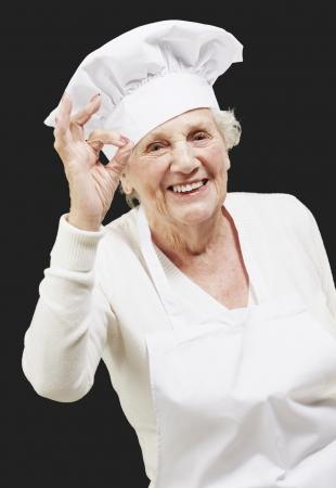 senior woman cook doing an excellent symbol against a black background