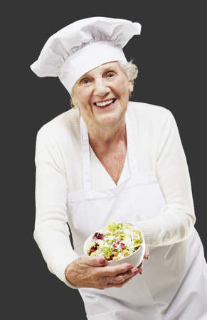 senior woman cook holding a bowl with salad against a black background Stock Photo - 13844547