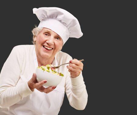portrait of senior cook woman eating salad over black Stock Photo - 13844531