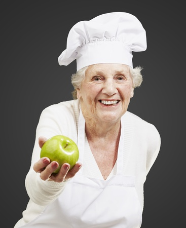senior woman cook offering a green apple against a black background photo