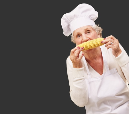 portrait of senior cook woman eating corn cob over black background photo