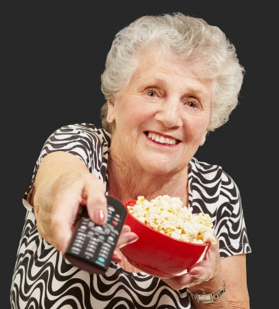 portrait of senior woman holding pop corn bowl and changing channel of tv over black background photo