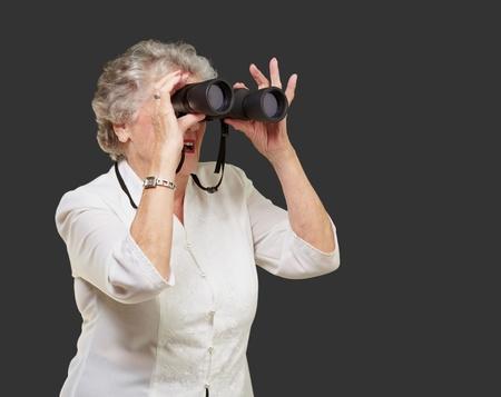 portrait of senior woman looking through a binoculars over black background photo
