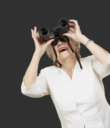 portrait of senior woman looking through a binoculars against a black background photo