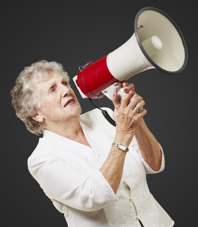 portrait of senior woman holding megaphone over black background photo