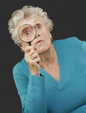portrait of senior woman looking through a magnifying glass over black background Stock Photo - 13844870