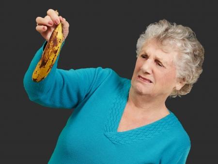 Senior woman holding a rotten banana over black background photo
