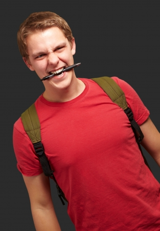 portrait of angry young man biting pen over black background Stock Photo - 13844735
