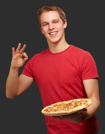 portrait of young man holding pizza and doing good gesture over black background photo