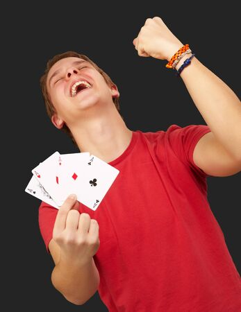 portrait of young man doing a winner gesture playing poker over black photo
