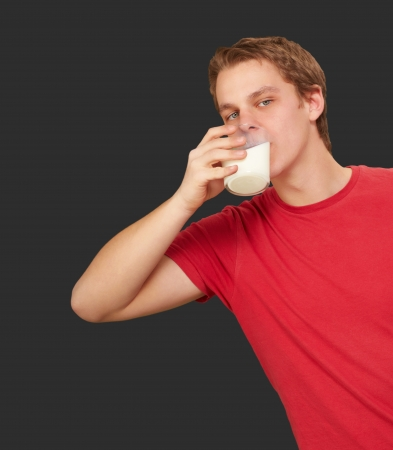 black hairs: portrait of young man drinking milk over black background