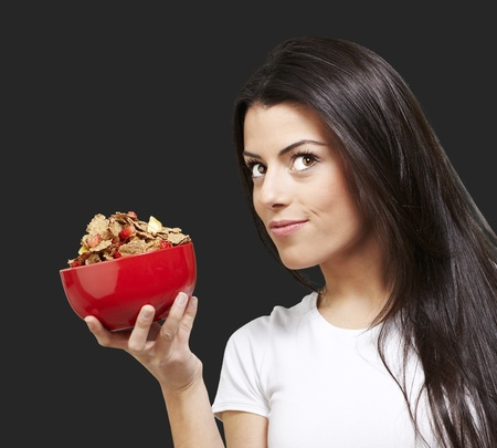 cornflakes: woman holding a delicious red breaksfast bowl against a black background