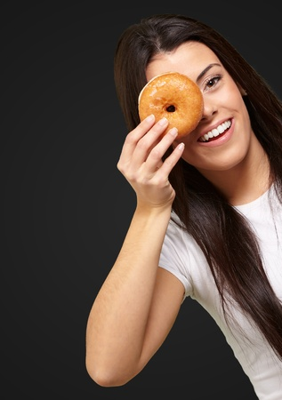 portrait of young woman looking through a donut over black Stock Photo - 13844454