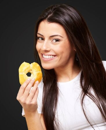 portrait of young woman eating a donut over black Stock Photo - 13844738