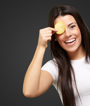 portrait of young woman holding a potato chip in front of her eye over black photo