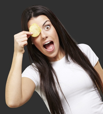 woman holding a potatoe chip in front of her eye against a black background Stock Photo - 13844548