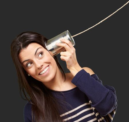Young woman hearing using a metal tin can over black background Stock Photo - 13844563
