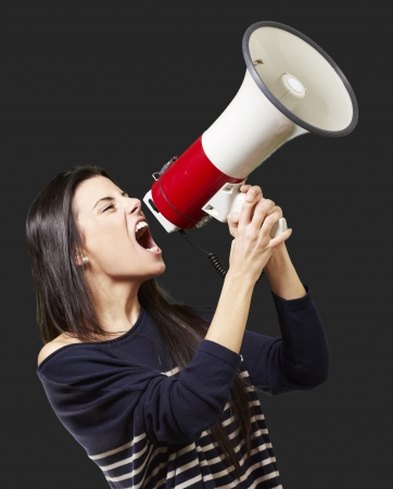 young woman shouting with a megaphone against a black background Stock Photo - 13844635