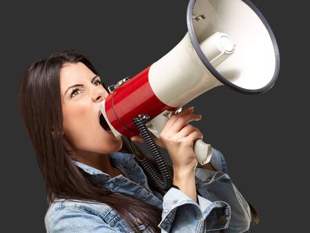 portrait of young woman screaming with megaphone against a black background Stock Photo - 13844478