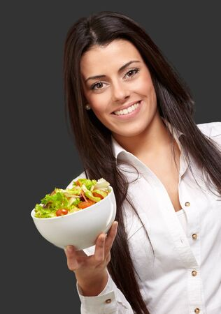 portrait of young woman holding salad over black Stock Photo - 13844762