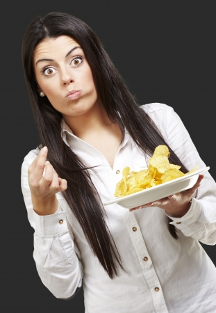 young woman eating potatoe chips against a black background Stock Photo - 13844579