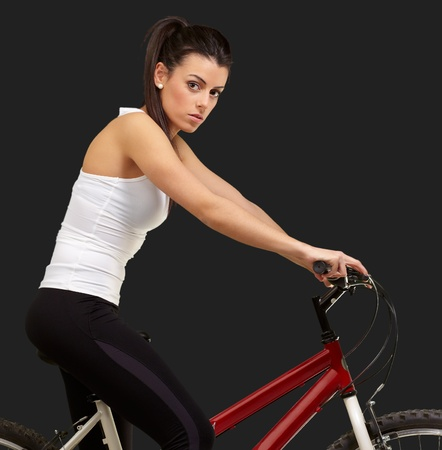 portrait of young woman cycling over black background photo