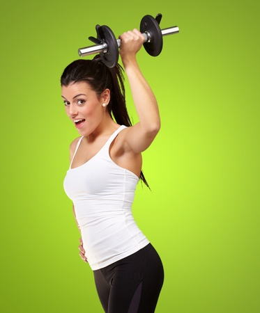 portrait of a young pretty woman holding weights and doing fitness over green photo