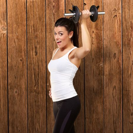 portrait of a young pretty woman holding weights and doing fitness against a wooden wall photo