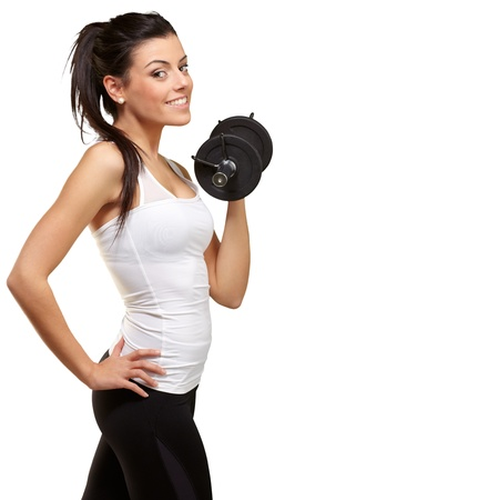 portrait of a young pretty woman holding weights and doing fitness against a white background photo