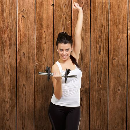 portrait of young woman doing fitness with weights against a wooden wall Stock Photo - 13844991