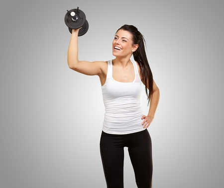 portrait of young girl training with weights over grey background photo