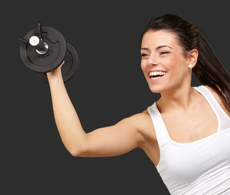 portrait of young girl training with weights over black background photo