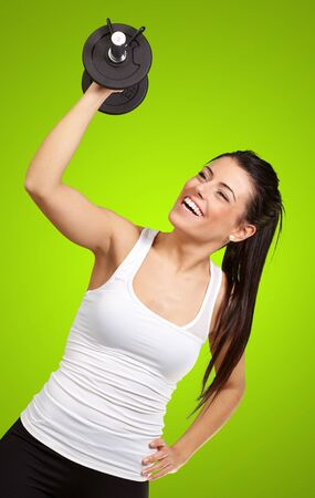 portrait of young girl training with weights over green background photo