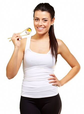 young woman holding a piece of sushi with chopsticks against a white background photo