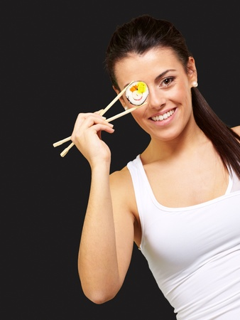 young woman covering her eye with a sushi piece against a black background photo