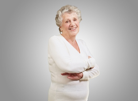 portrait of senior woman smiling over grey background photo