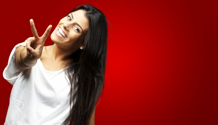 Happy Young Woman Showing Victory Sign On Red Background  photo