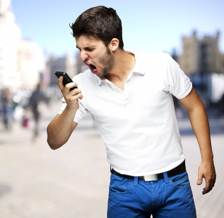 young man shouting at a phone against a street background photo