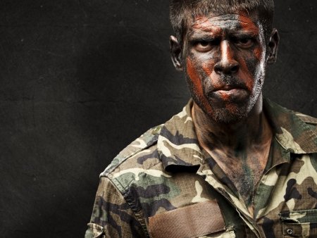 elite: young soldier with camouflage paint looking very serious against a grunge wall