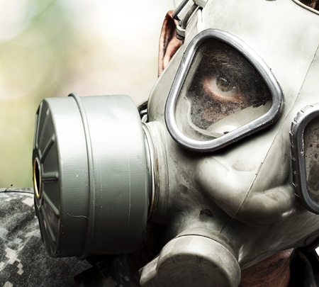 portrait of young soldier wearing gas mask against a nature background photo