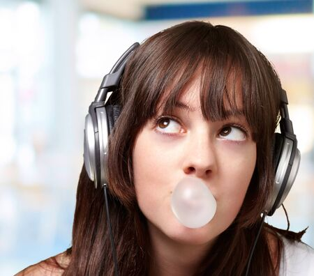 home audio: portrait of young woman listening to music with bubble gum over abstract background