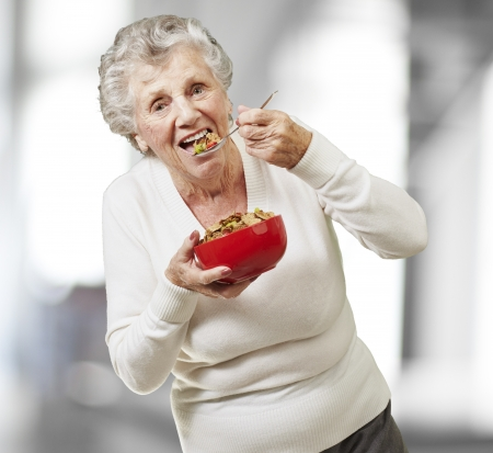 senior woman eating cereals out of a red bowl, indoor photo