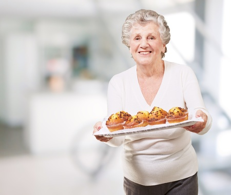 senior home: portrait of senior woman showing a chocolate muffin tray indoor