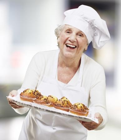 cozimento: S�nior, mulher cozinheiro segurando uma bandeja com muffins, interiores Banco de Imagens