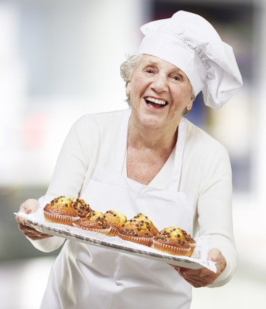 baking bread: senior woman cook holding a tray with muffins, indoor