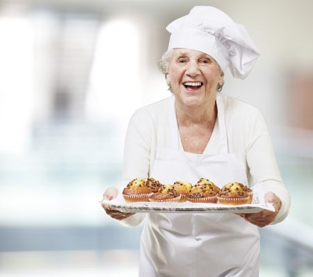 baking tray: senior woman cook holding a tray with muffins, indoor