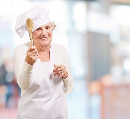 portrait of senior cook woman holding a wooden spoon indoor photo