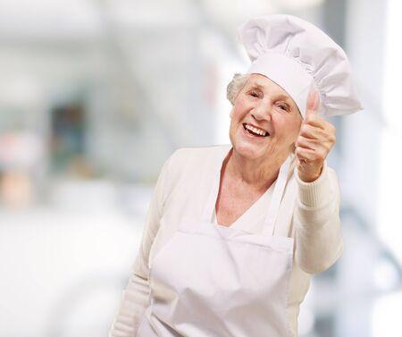 portrait of cook senior woman doing good gesture indoor photo